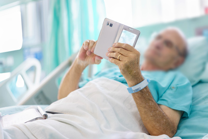 Mature male patient playing a mobile on bed in hospital